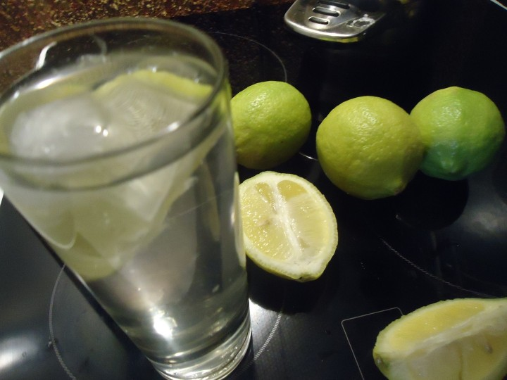 Glass of lemon water on kitchen table. 14 day challenge lemon and water diet review